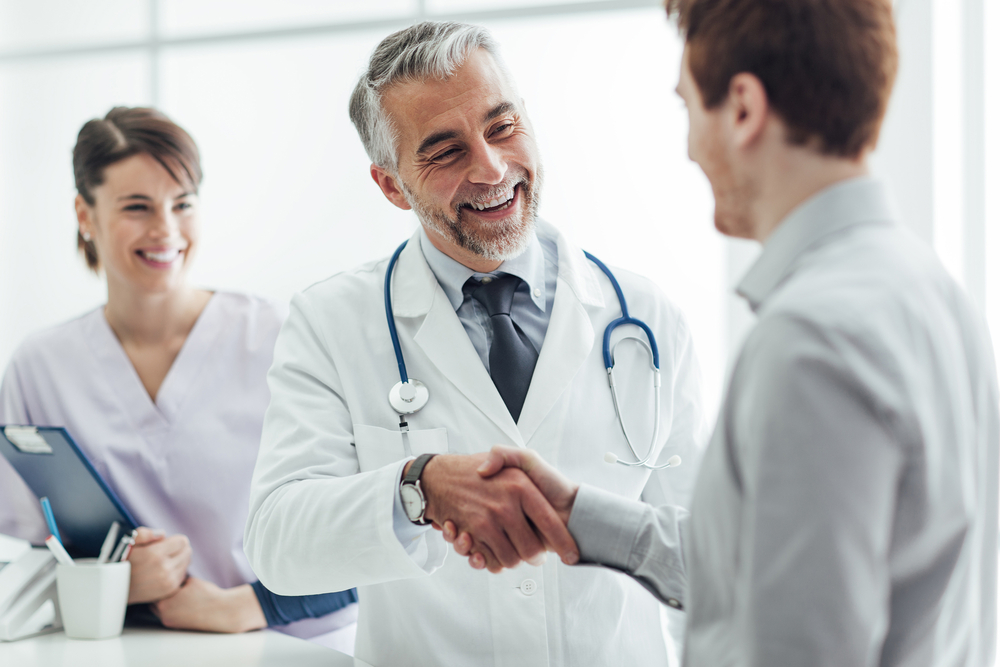 An older doctor shaking hands with his male patient