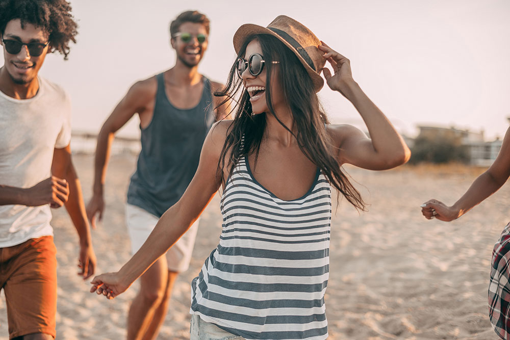 A young woman jogging on the beach and smiling with her friends