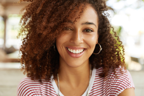 A smiling young woman with curly hair