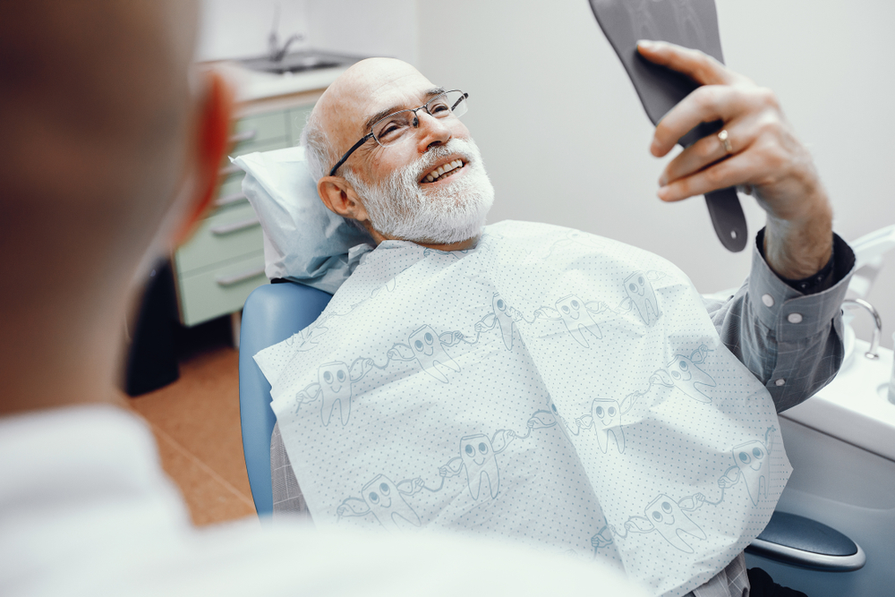 A man looks at the results of his dental implant procedure after waking up from sedation dentistry.