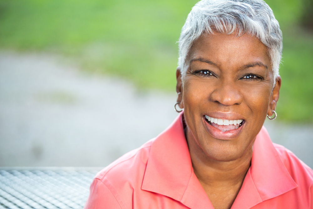 A woman shows off her beautiful smile thanks to sedation dentistry and dental implants.