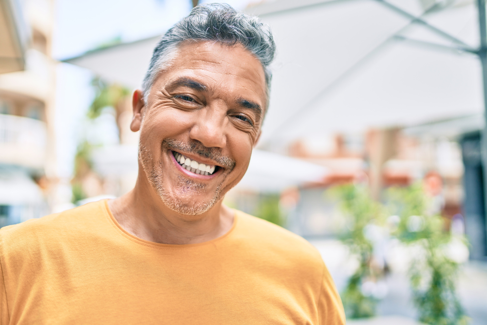 A man smiles following his teeth in a day procedure.